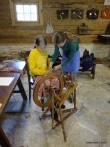 Tüdruk õpetab tüdrukule ketramist